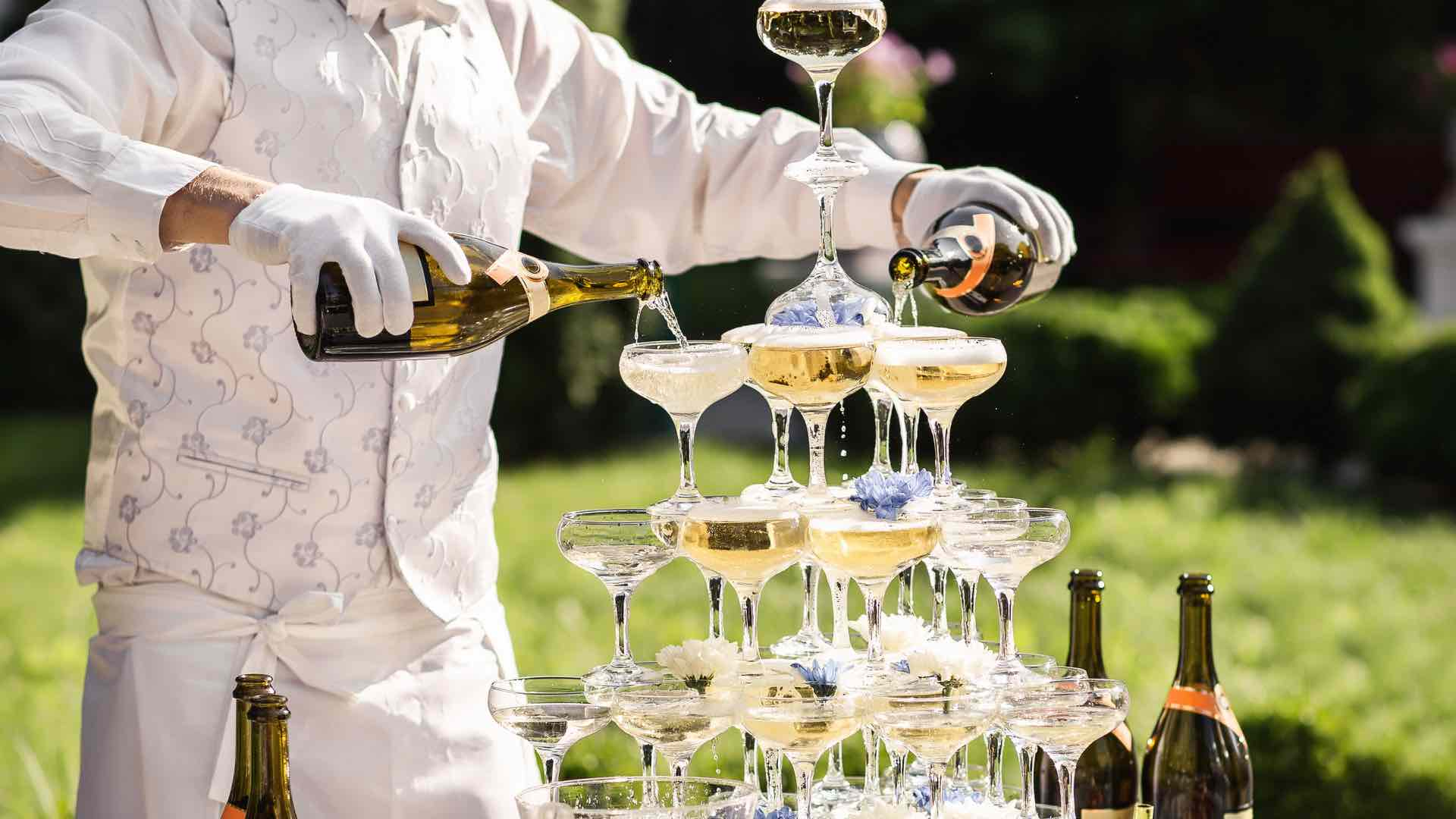 Mann schenkt Sekt in Glas + Cocktail Catering