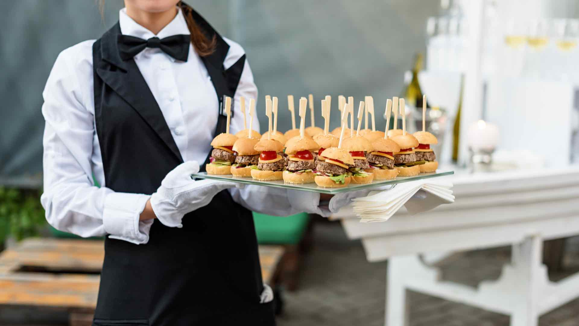 Caterer hat Tablet mit Speisen in der Hand + Party Service